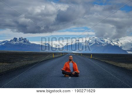 Travel hitchhiker man meditating on a road