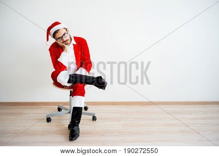 A portrait of a bored Santa Claus sitting on a chair