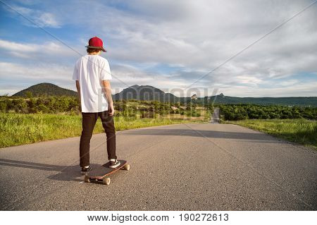 A young guy - a skater in a cap stands in anticipation of a race on a country road against the backdrop of a beautiful landscape