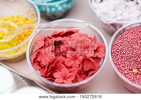 Ice cream treats and toppings sale. Rainbow sprinkles, non pareil and flower form glitter cupcake decorations, bright pink and red. Closeup in plastic plates with spoons. Confectionery store