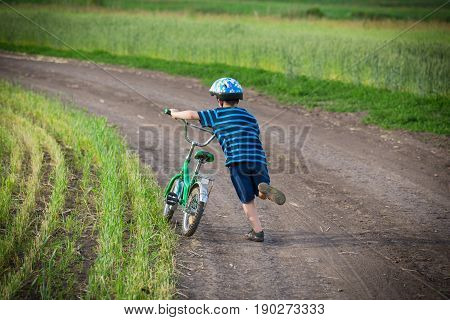 Little boy walking uphill with his bike on rural landscape, outdoors