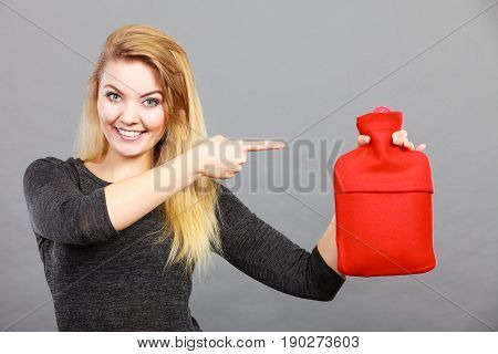 Positive smiling woman recommending warm hot water bottle in red soft fleece cover on grey. Health care pain relievers recovery concept.