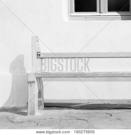 Chair In The Greece Island Of Paros Old Bench Near A Brick Antique Wall And Stone Pavement