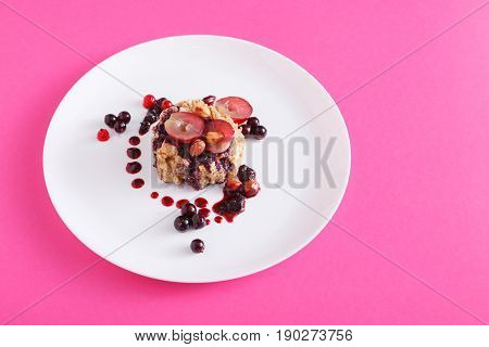 Healthy breakfast on pink, dieting and detox concept - wholegrain fresh oatmeal porridge on plate with fruits, berries and nuts.