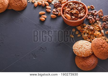 Healthy organic oat cookies made of wholegrain oat and nuts on dark table background, free copy space. Flat lay, mockup, template, objects, nobody