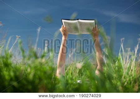 A woman lies on a grass and reads a book outside, woman keep keep hands with book up