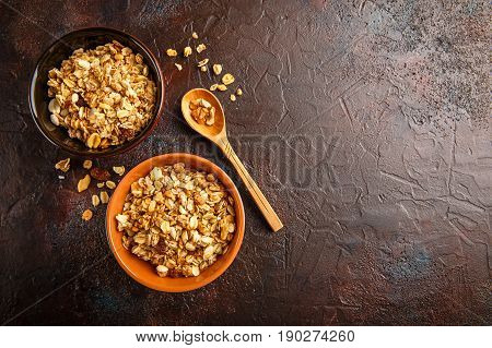 Delicious homemade granola or muesli inwppden spoon on stone background. Top view. Place for text.