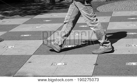 Big chess on the square walking man in the city