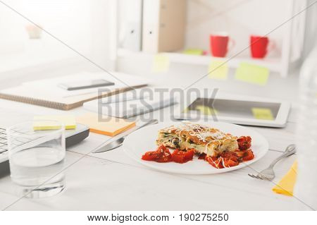 Healthy lunch in office, selective focus on steamed fat free lasagna dish at desk. Restaurant food on office table with mobile phone, papers and laptop at background. Diet meals concept