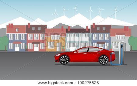 Electric car stands near the station and is charged against the background of city houses and mountains, on top of which are located wind turbines.