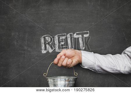 Cropped image of businessman holding metallic bucket under REIT text on blackboard