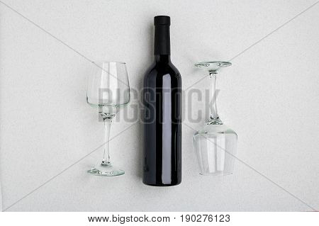 Overhead angled view of a large bottle of red wine, drinking glasses on white background. Top view. Copy space