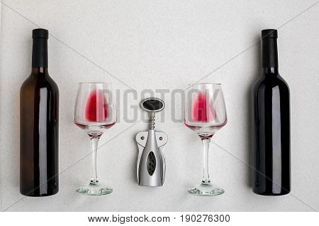 Glasses and bottles of red and white wine on white background from top view. Copy space