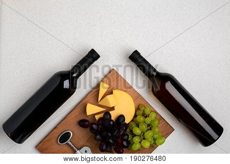 Bottles of red and white wine on white background from top view. Copy space