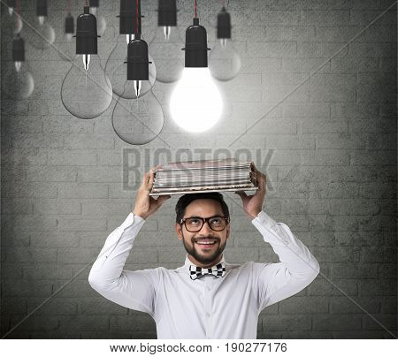 Businessman carrying book on head with glowing light bulb
