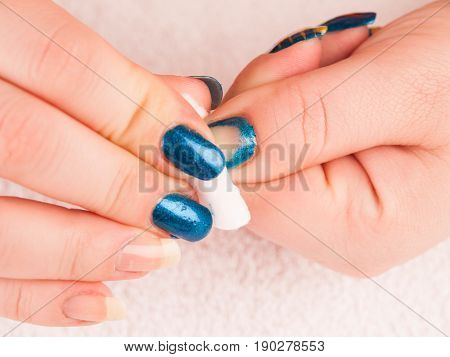 Cleaning blue polish from fingers using cleansing cotton pad