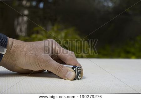 Male hand holding a 9 volt battery on a table top outdoor cropped shot