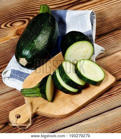 Fresh Raw Zucchini Full Body and Slices on Cutting Board closeup on Wooden background