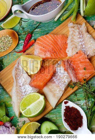 Food Background of Raw Thai Fish Cakes Ingredients with Vegetables Spices Herbs Fruits Prawns and Delicious Fillet of Salmon and Cod closeup on Cracked Wooden background