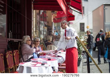 Paris, France - May 12, 2017: A waiter serving customers in the outside area of a restaurant in Montmartre district