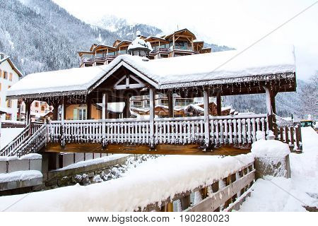 bridge covered with snow and alpine style houses in Chamonix mont blanc town in French Alps, France