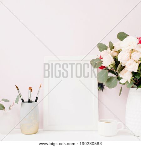 Home office desk with photo frame mock up beautiful roses and eucalyptus bouquet in front of pale pastel pink background. Blog website or social media concept .