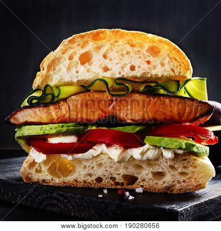 Ultimate sandwich with grilled salmon cream cheese sliced avocado and seasonals on black wooden board with free text space.