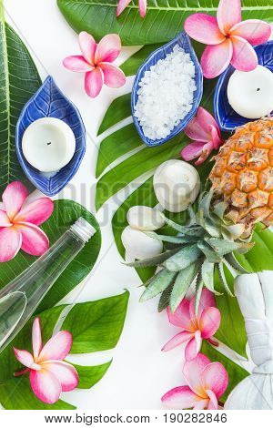 Spa botanical tropical concept herb salt coconut oil and plumeria flowers on tropic leaf background flat lay top view