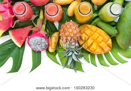 Tropic flat lay top view tropical summer concept with colorful tropical fruits mango pineapple dragon watermelon apple orange banana lime and smoothie juice palm leaves and plumeria on white.
