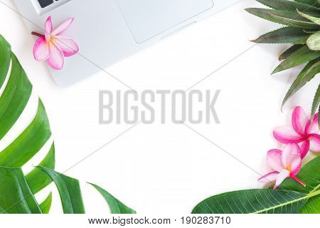 Tropic flat lay top view tropical summer botanical concept with laptop pineapple palm leaves and plumeria on white