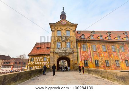 Bamberg, Germany - February 19, 2017: Icon of Bamberg Obere bridge or brucke and Altes Rathaus town hall city center, people