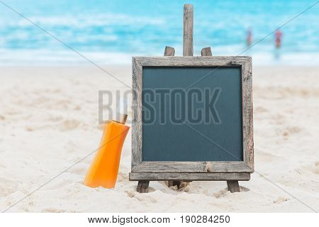 Chalk board with sunscreen cream in the sand on the beach tropic exotic background
