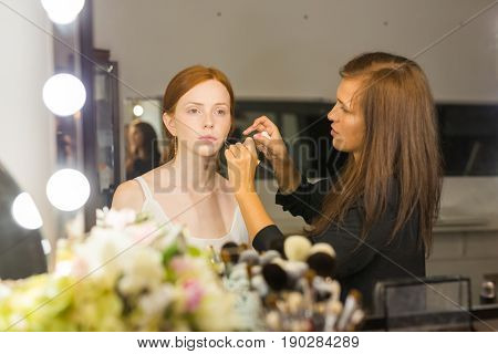 Process of making makeup. Make-up artist working with brush on model face. Portrait of young red hair woman in beauty saloon interior. Applying tone to skin