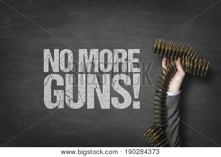 Cropped image of businessman's hand holding bullets by no more guns text on blackboard