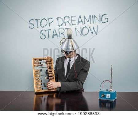 Stop dreaming start  now text on blackboard with businessman and abacus