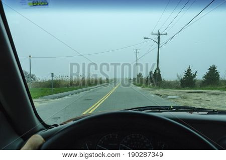 Driving down two-lane road on hazy morning