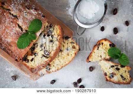 Traditional cake with raisins sprinkled with powdered sugar and mint leaves decorated. At Marble gray background, top view