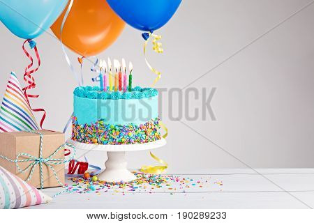 Blue Birthday cake presents hats and colorful balloons over light grey.