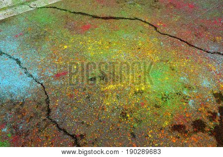Multi-colored asphalt after a youth festival of paints