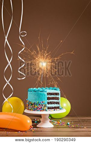 Blue Birthday cake with sparkler and colorful balloons.