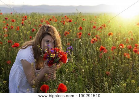 Woman in white dress smelling a bouquet of poppies standing on the field