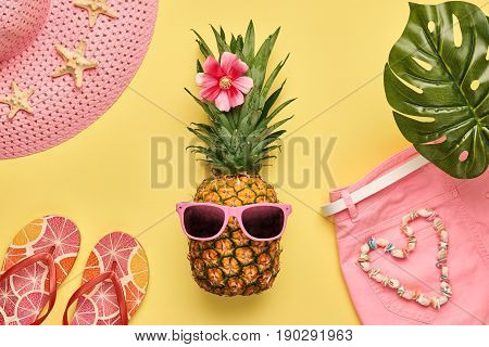 Fashion Pineapple. Bright Summer Color. Clothes Accessories set. Creative Art concept. Fashion woman Swimsuit Bikini, Tropical pineapple. Stylish girl. Minimal. Summer background on yellow. Top View