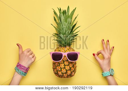 Fashion Hipster Pineapple. Female hand OK, YES Gesture Stylish Trendy Watches, Glamor Accessories. Bright Summer Color. Tropical pineapple, Sunglasses. Creative Art concept. Minimal. Summer background