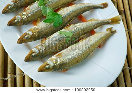baked smelt served with roasted carrots. close up