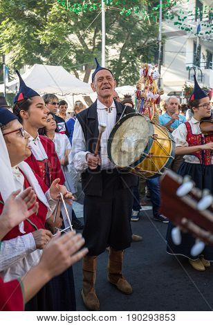 ESTREITO DE CAMARA DE LOBOS PORTUGAL - SEPTEMBER 10 2016: Folk music group in local costumes performs a folk dance at Madeira Wine Festival in Esterito de Camara de Lobos on the Madeira Portugal. The Madeira Wine Festival honors the grape harvest with a c