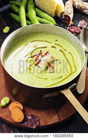 Fava beans cream soup with pecorino cheese olive oil and salami in copper pot on dark rustic table italian food concept .