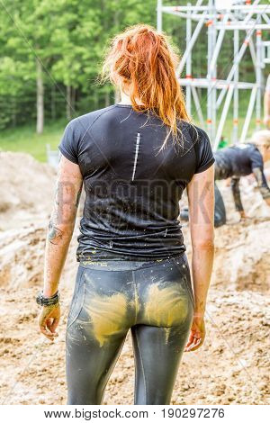 Stockholm Sweden - June 03 2017: Close up back view one caucasian woman with dirty muddy outfit looking at a mud obstacle after completing the course of the annual event Toughest Stockholm. People in the background.