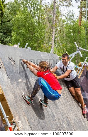 Stockholm Sweden - June 03 2017: Side view of man and woman athlete climbing a wooden obstacle to complete the annual obstacle course event Toughest Stockholm.