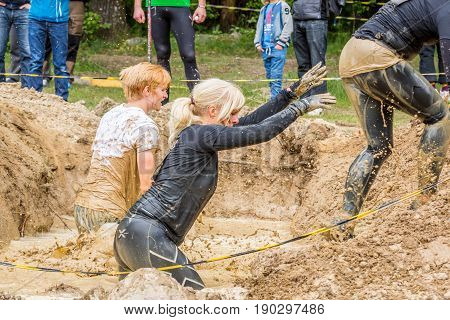 Stockholm Sweden - June 03 2017: Close up side view three caucasian woman struggling in a mud obstacle to complete the course of the annual event Toughest Stockholm. Water splash and people in the background.