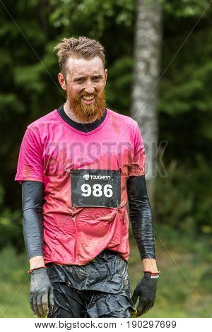 Stockholm Sweden - June 03 2017: Close up front view one caucasian man with full beard. Wet dirty and tired after completing a mud obstacle at the annual event Toughest Stockholm.
